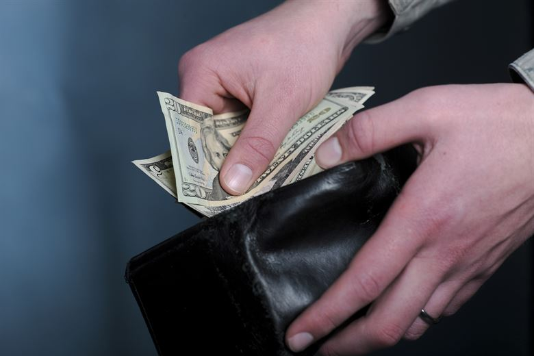 Image of Money being placed in a wallet